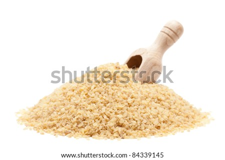 Raw dried couscous with wooden scoop isolated on white background