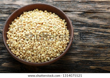 Raw dry peas in a plate on a brown wooden table. space for text
