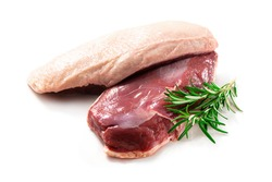 Raw duck breast pieces garnished with parsley and rosemary isolated on white background