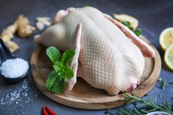 Raw duck with herb spices ready to cook on dark plate, Fresh duck meat on wooden tray for food, Whole duck - close up