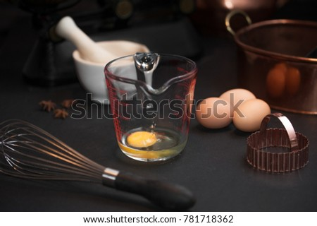 Raw eggs prepared for whisking, a whisk, white mortar with anise stars, vintage copper baking shape #781718362