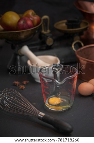 Raw eggs prepared for whisking, a whisk, white mortar with anise stars, vintage scale with apples and copper baking form #781718260