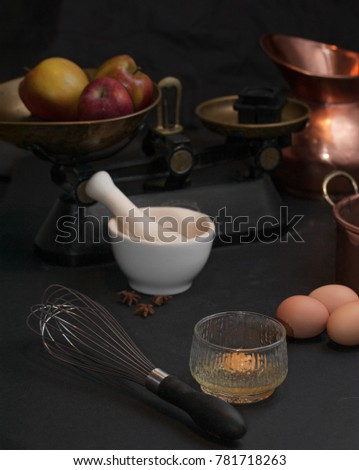 Raw eggs prepared for whisking, a whisk, white mortar with anise stars, vintage scale with apples and copper baking form #781718263