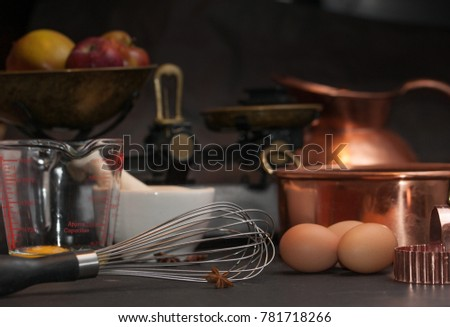 Raw eggs prepared for whisking, a whisk, white mortar with anise stars, vintage scale with apples and copper baking form #781718266