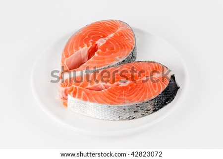 Raw fillet of fresh salmon fish on white plate
