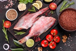 Raw fillet of red sea perch prepared for baking with spices and herbs on a dark background