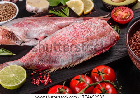Photo of  Raw fillet of red sea perch prepared for baking with spices and herbs on a dark background