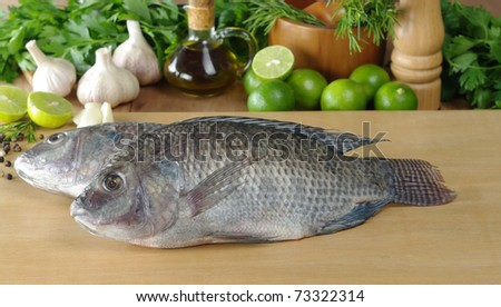 Raw fish called tilapia on cutting board surrounded by spices, herbs and seasonings (Selective Focus, Focus on the head and the body of the first fish)