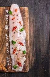 raw Fish fillet with herbs and spices on cutting board , top view