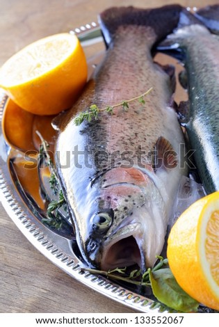 raw fish trout on ice with lemon and thyme