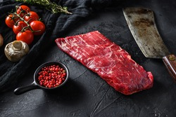 Raw, flap or flank, also known Bavette steak near butcher knife with pink pepper and rosemary. Black stone background. Side view vertical