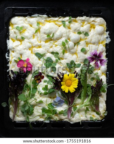 raw floral painting focaccia, garden flatbread art, eatable flowers food trend. black tray background, top view