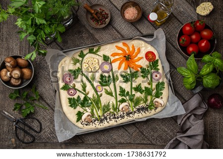 raw floral painting focaccia,  garden flatbread art, food trend. Old wooden background, top view