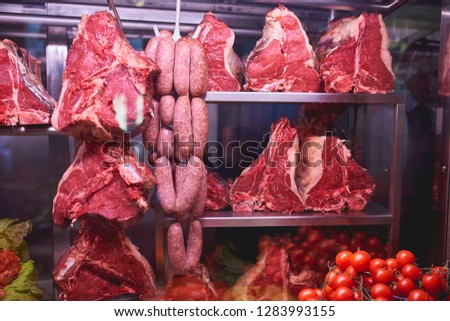 Raw Florentine steaks (bistecca alla Fiorentina) and Sausages in a typical trattoria in Florence (Italy). Landscape format. Food concept.
