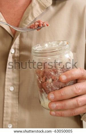 Raw Foodism.  Man eating raw beef with cream and butter from glass jar.