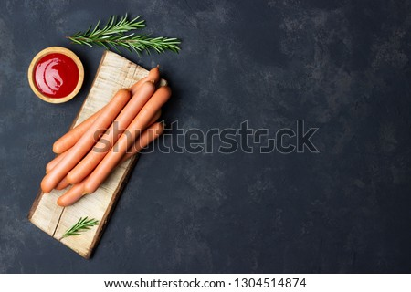 Raw frankfurter sausages with ketchup on cutting board. Top view. Copy space for text.