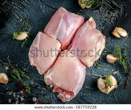 Raw Free range Boneless skinless chicken thighs with thime, garlic, red pepper corns and sea salt flakes on stone table ストックフォト ©