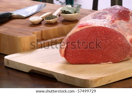 raw fresh and juicy eye of round roast steak or beef  with ingredients on background  perfect for baking and roasting