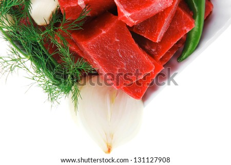 raw fresh beef meat slices in a white bowls with dill and green hot peppers isolated over white background