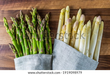 raw fresh bunch of green and white asparagus in grey cloth on rustic wood board Foto d'archivio ©