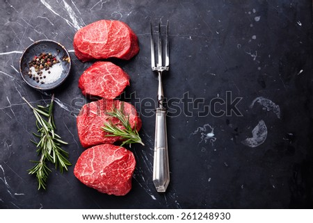 Raw fresh marbled meat Steak, seasonings and meat fork on dark marble background