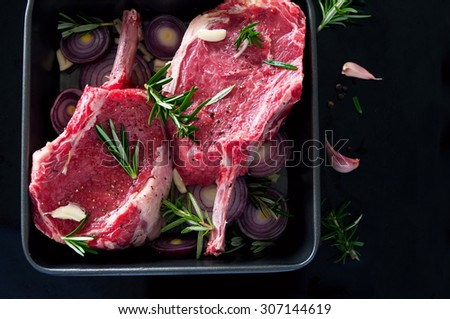 Raw fresh meat beef steak, seasonings with salt, pepper, rosemary leaves and red onion, on a black tray ready to be cooked, top view, copy space. Black background, healthy lifestyle #307144619