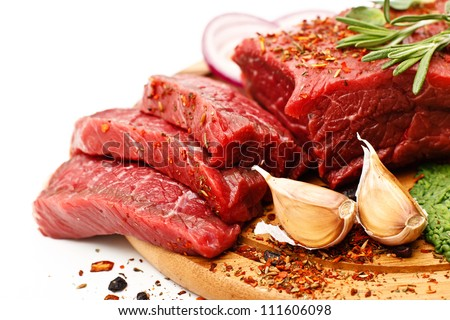 Raw fresh meat on board with condiments on white background