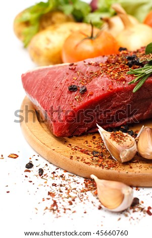 Raw fresh meat on board with vegetables on white background