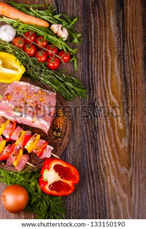 Raw fresh meat on cutting board with condiments and fresh vegetables