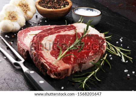 Raw fresh meat Ribeye Steak, seasoning and meat fork on a table
