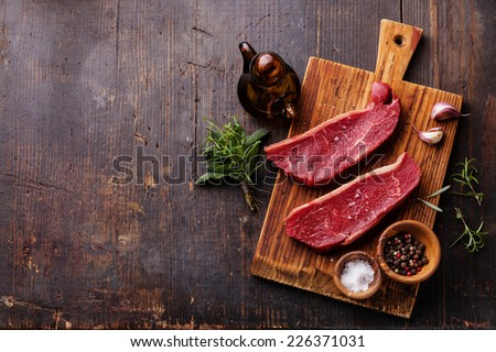 Raw fresh meat Striploin steak and seasoning on dark wooden background #226371031