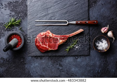 Raw fresh meat Veal rib Steak on bone and seasonings on dark background #483343882
