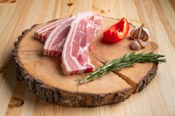 Raw fresh pork brisket slices on wooden cutting board