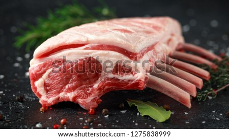 Photo of  raw fresh rack of lamb with green herbs.