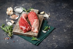 Raw Fresh Steak Sirloin Flap Served with Rosemary, garlic and spices on Wooden cutting Board. Black Angus Beef Meat. Place for text