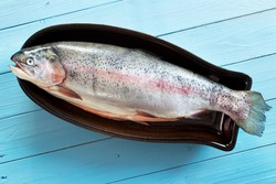 Raw fresh steelhead trout on ceramic oven fish tray , top view , on wooden surface