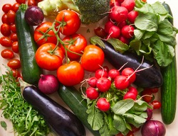 Raw fresh vegetables background. Healthy food flat lay on wooden background. Assortment of organic red and green vegetables: tomato, radish, broccoli, aubergine, cucumber, rucola, red onion, broccoli