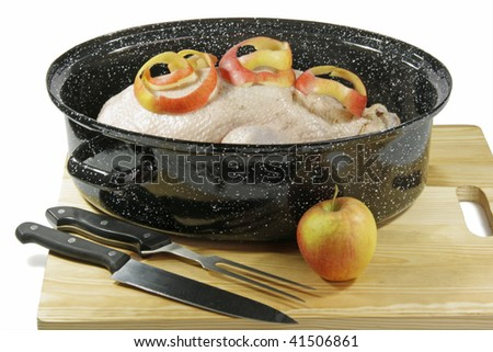 Raw goose stuffed with apples in a pot