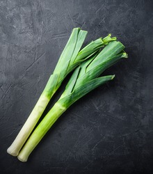 Raw Green Organic Leeks on black textured background, top view.