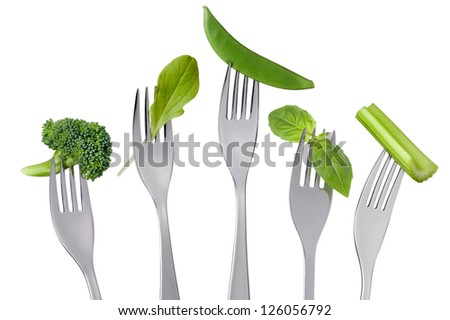 raw green vegetables on forks isolated against white background