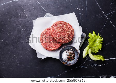 Raw Ground beef meat Burger steak cutlets and seasonings on dark marble background