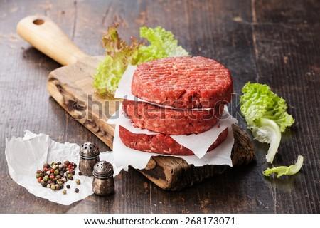 Raw Ground beef meat Burger steak cutlets and seasonings on dark wooden background