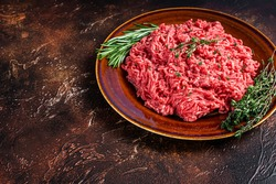 Raw ground beef or veal meat on a rustic plate with herbs. Dark background. Top view. Copy space