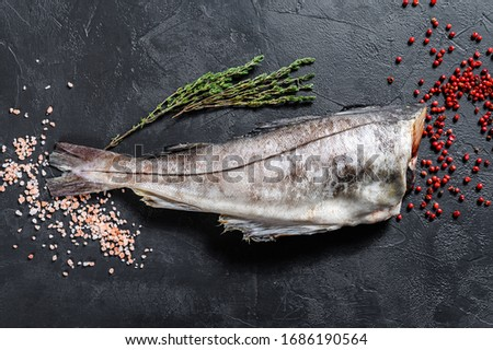 Raw haddock fish without a head. Black background. Top view ストックフォト ©