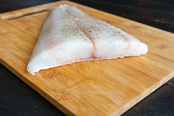 Raw Halibut Fillet on a Bamboo Cutting Board: Uncooked white fish fillet seasoned with salt and pepper