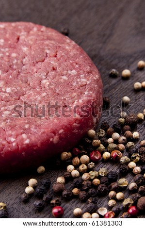 raw hamburger on a wooden board with spices