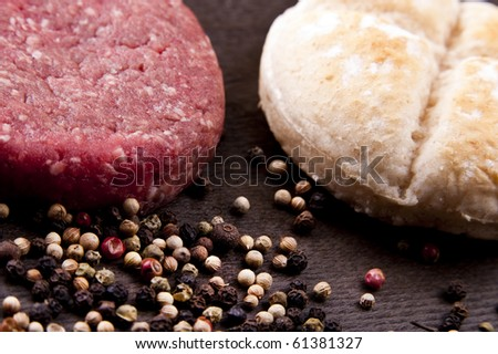 raw hamburger on a wooden board with spices and burger bun