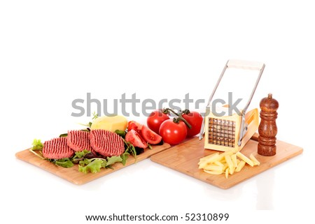 Raw hamburgers, tomatoes and peeled potato on cutting board, French fries cutter and pepper mill on the side,  on reflective surface, studio, white background.
