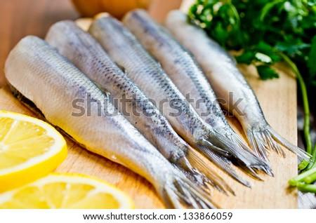 Raw herrings on wooden board