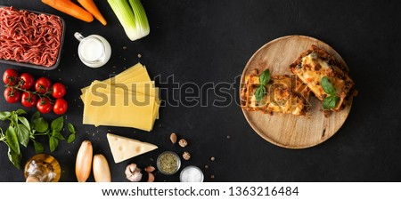 Raw ingredients and products for pasta and lasagna backdrop. Top view and flat lay of vegetables, herbs and ready lasagna meal on a black concrete stone background